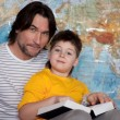 Stock Photo: Dad and son reading a book on a map of the world