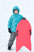 The boy with red sleds in winter — Stock Photo