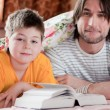 Stock Photo: Dad and son reading in bed