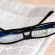 Eyeglasses lying around newspapers — Stock Photo