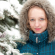 Young woman in snow-covered spruce forest — Stockfoto