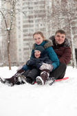 Young family rides to the hills on sleds — Stock Photo