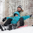 Dad and son riding a frozen hill - Stock Photo