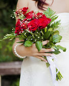 Wedding bouquet with red rosesat bride's hands — Stock Photo
