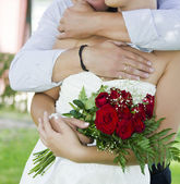 Groom and bride with wedding bouquet — Stock Photo
