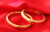 Gold wedding rings on red satin — Stock Photo