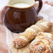 A jug with milk and lye pastry on the wooden board — Stock Photo
