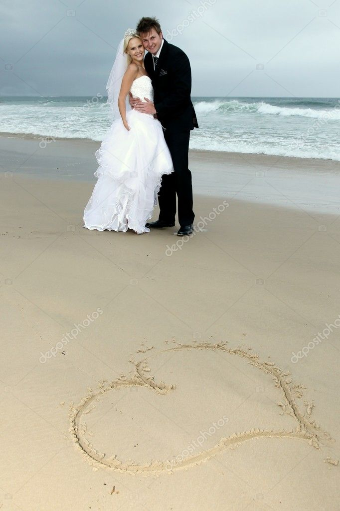 Pretty blond bride and her handsome groom at the sea shore — Stock Photo #8504220
