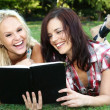 Beautiful Young Women Friends Reading Outdoors — Stock Photo