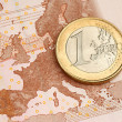 One Euro Coin on Euro Banknote showing Map of Europe — Stock Photo #10165338