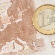 Stock Photo: One Euro Coin on Euro Banknote showing Map of Europe
