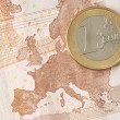 One Euro Coin on Euro Banknote showing Map of Europe — Stock Photo
