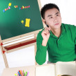 Student setting by a desk in the front of the blackboard. — Stock Photo #9463923