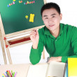 Student setting by a desk in the front of the blackboard. — Stock Photo #9464261