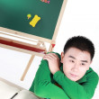 Stock Photo: Student setting by a desk in the front of the blackboard.