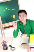Student setting by a desk in the front of the blackboard. — Stock Photo