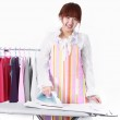 A Chinese woman is using a electric iron with many clothing. — Stock Photo