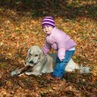 Little girl with her dog in an autumn woods — Foto de Stock