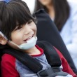 Stock Photo: Happy five year old disabled boy in wheelchair and protective ge