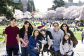 Family of seven in front of cherry blossom trees — Stock Photo
