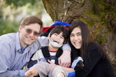 Disabled boy in wheelcahir surrounded by father and sister — Stock Photo