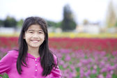 Ten year old girl smiling in front of tulip fields — Stock Photo