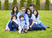 Large family of seven sitting together on lawn, dressed in blue — Stock Photo