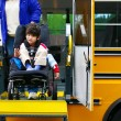 Disabled five year old boy using a bus lift for his wheelchair - Stock Photo