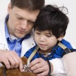 Stock Photo: Male doctor interacting with disabled toddler patient on lap