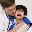Stock Photo: Male doctor comforting scared toddler patient.