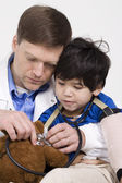 Male doctor interacting with disabled toddler patient on lap — Stock Photo