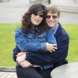 Foto Stock: Beautiful Caucasian, Asicouple sitting outdoors together, hug