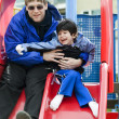 Father going down slide with disabled son who has cerebral palsy - Stockfoto
