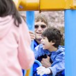 Father playing at playground with disabled son - Stock Photo