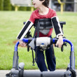 Stock Photo: Five year old disabled boy in walker by park. He has cerebral pa