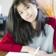 Stock Photo: Ten year old girl writing or drawing on paper