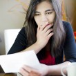 Teenage girl or young woman reading a note, worried expression — Stock Photo #9134655