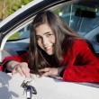 Teenage girl in driver's seat holding keys - Stock Photo