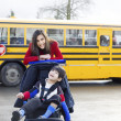 Big sister with disabled brother in wheelchair by school bus — Stock Photo #9134672