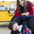 Stock Photo: Big sister with disabled brother in wheelchair by school bus