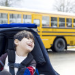 Disabled five year old boy in wheelchair, by schoolbus - Stock Photo