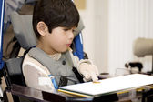 Five year old disabled boy studying in wheelchair — Stock Photo
