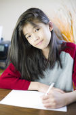 Ten year old girl writing or drawing on paper — Stock Photo