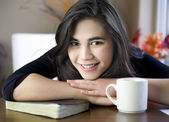 Teenage or young woman at table with Bible and coffee cup — Stock Photo