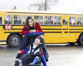 Big sister with disabled brother in wheelchair by school bus — Foto de Stock