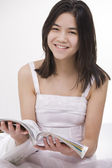 Beautiful young teen girl in white dress sitting reading a magaz — Stock Photo