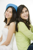 Two young teen girls back to back sitting together, isolated on — Stock Photo