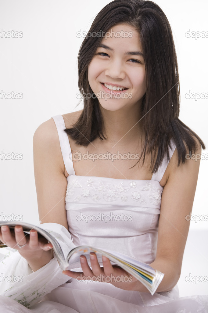 Beautiful young teen girl in white dress sitting reading a magazine, ...