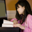 Stock Photo: Ten year old Asigirl reading at desk, by computer