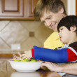 Stock Photo: Father helping disabled son with work in kitchen